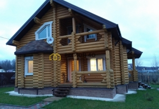 Дом из бревна для проживания в окружении леса и охраняемом поселке