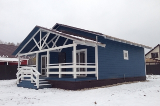 Зимний одноэтажный дом из бруса в деревне.